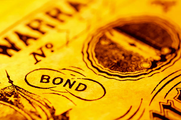 a close-up of the word bond with a yellow tint - stock certificate stock photos and pictures