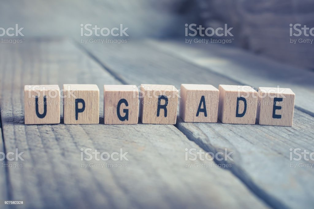 Closeup Of The Word Upgrade Formed By Wooden Blocks On A Wooden Floor stock photo