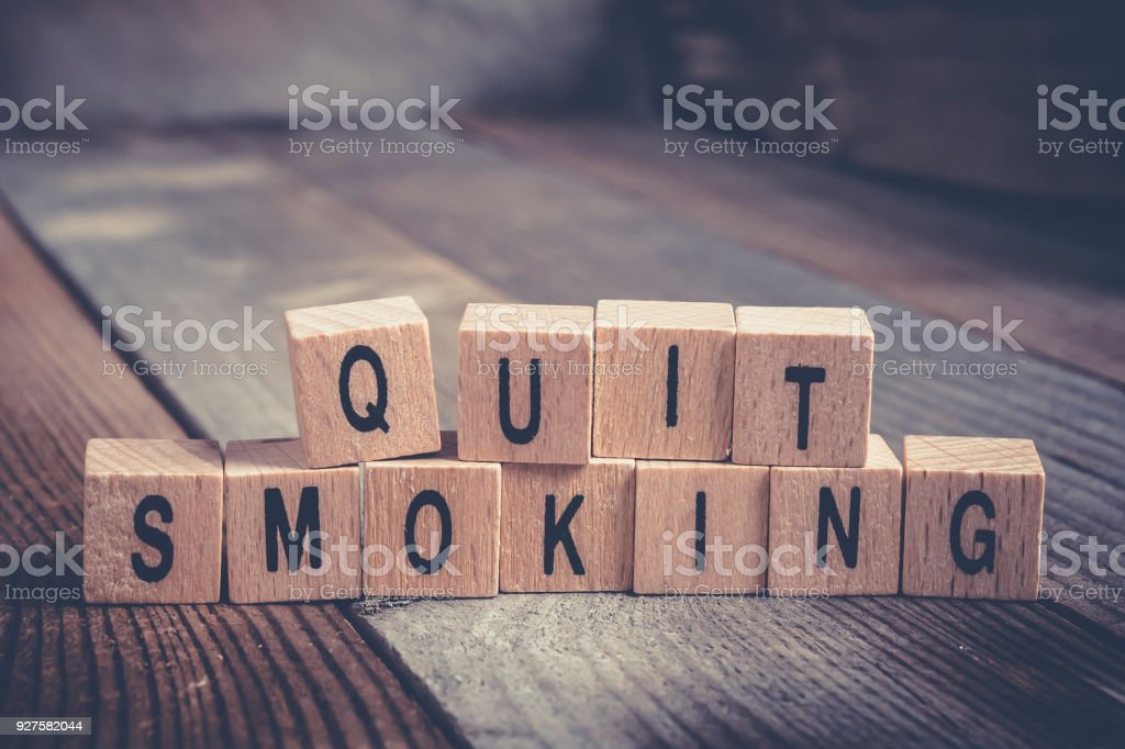 Closeup Of The Words Quit Smoking Formed By Wooden Blocks On A Wooden Floor stock photo