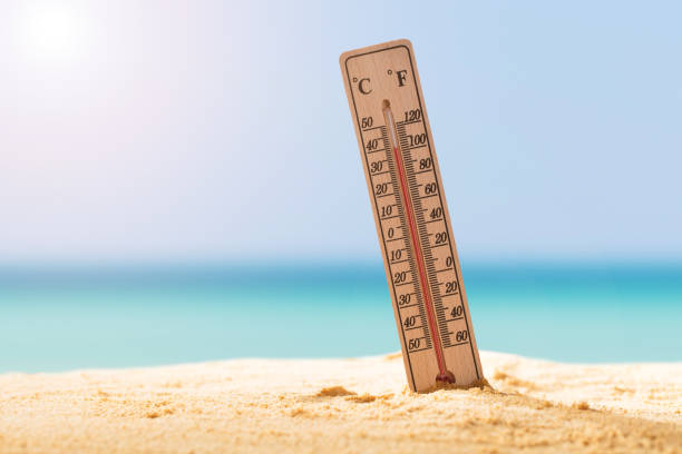 close-up of thermometer on sand - weather stock photos and pictures