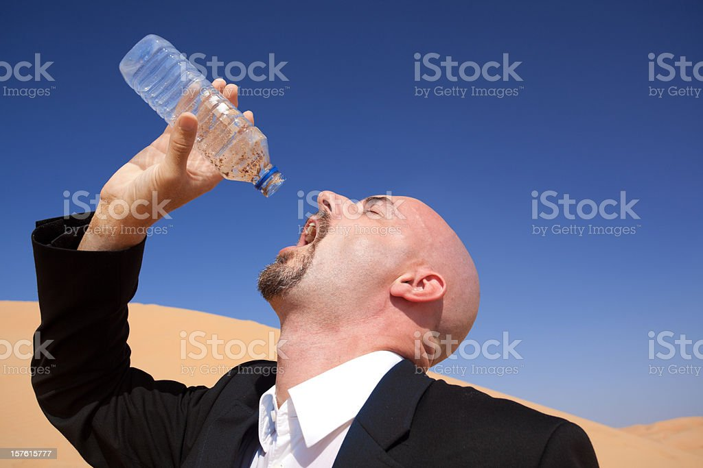 closeup of thirsty businessman with empty water bottle royalty-free stock photo