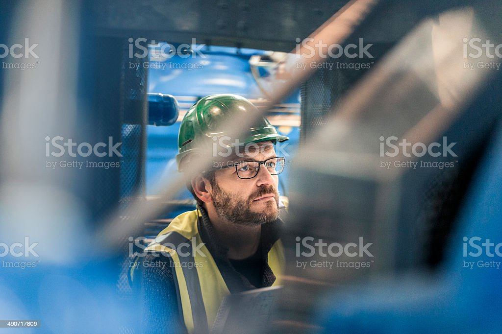 Close-up of thoughtful male manual worker at factory stock photo