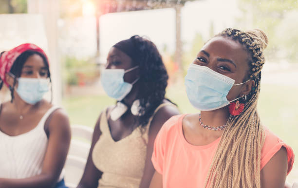 Close-up of three African American girls wearing surgical masks.