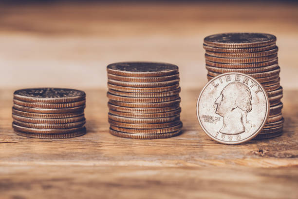 Closeup of three american quarters stacks with a coin on the face side standing against the highest pile. Free trade, economy, liberalism, capitalism concepts. stock photo