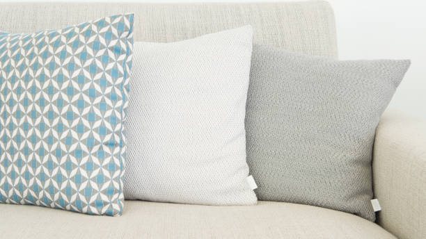 Close-up of three different sizes cushions in soft, pastel colors Horizontal shot of almost monochrome cushions, positioned on a beige, textile sofa, very modern, minimalist interior design detail for a cozy home. cushion stock pictures, royalty-free photos & images