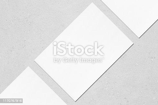 1171907064 istock photo Closeup of three empty white rectangle poster mockups lying diagonally on grey concrete background 1170767916