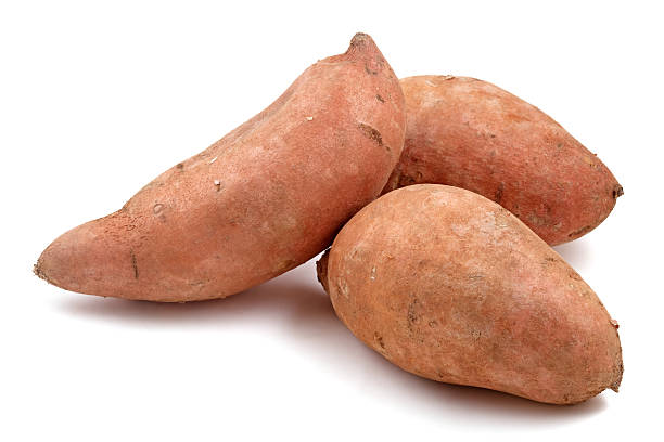 Close-up of three Raw sweet potatoes Three sweet potatoes isolated on white. sweet potato stock pictures, royalty-free photos & images