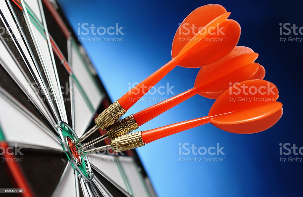 Close-up of three red darts in a bullseye stock photo