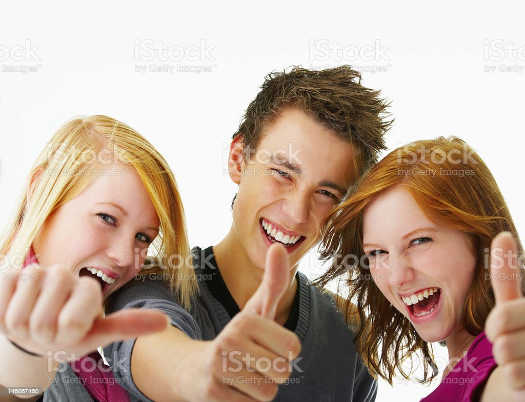 Close-up of three teenagers laughing and gesturing thumbs-up sign stock photo