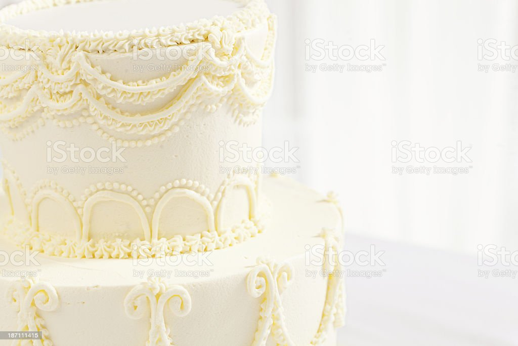 Close-up of Tiered Wedding Cake with Cream Frosting Vertical royalty-free stock photo