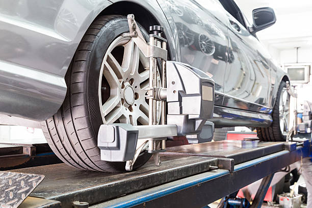 Closeup of tire clamped with aligner undergoing auto wheel align stock photo