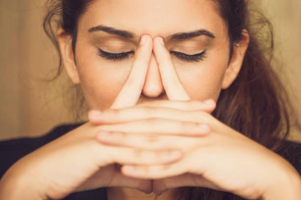 close-up of tired young woman rubbing nose - strofinare toccare foto e immagini stock