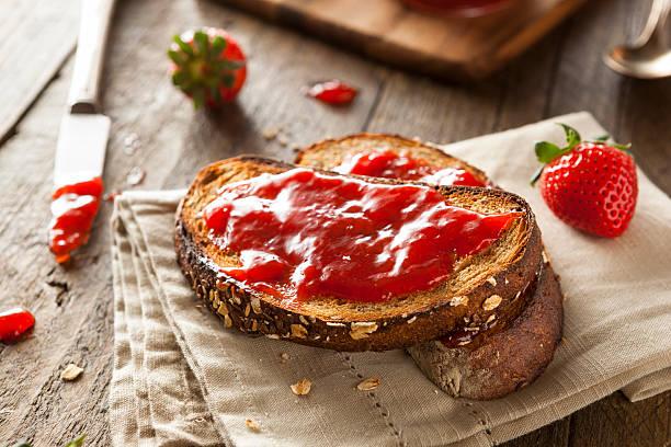 marmellata di fragole fatta in casa su pane tostato - marmellata foto e immagini stock