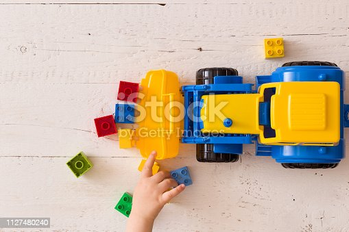 istock Closeup of toddler boy's hands playing with colorful toy tractor. Child playing with a car at a nursery or preschool. 1127480240