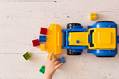Closeup of toddler boy's hands playing with colorful toy tractor. Child playing with a car at a nursery or preschool.