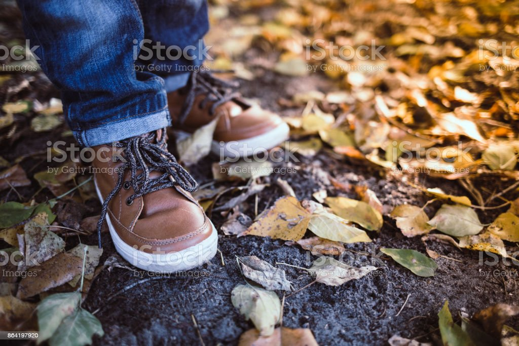 Closeup of toddler's boots on bright autumn leaves background. Child walking in the park. royalty-free stock photo