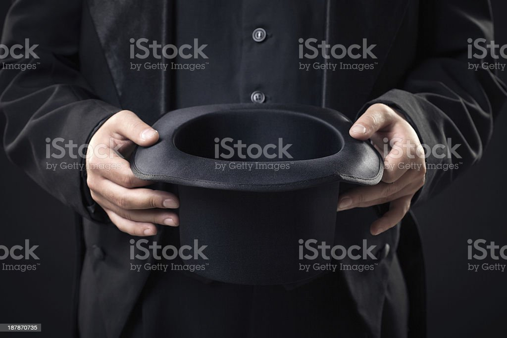 closeup of top hat in magician hands isolated on dark stock photo