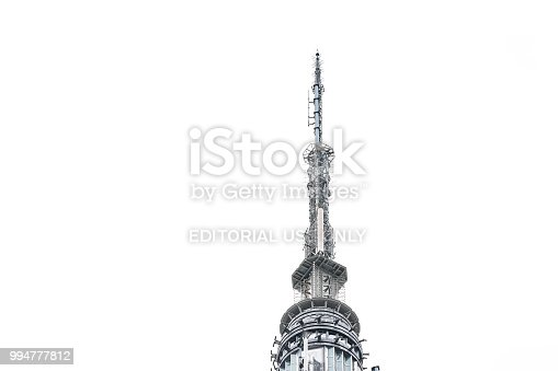 New York City, USA - April 7, 2018: Closeup of top of empire state building spire isolated against cloudy white sky during day rooftop famous iconic building in NYC Herald Square Midtown, high tall