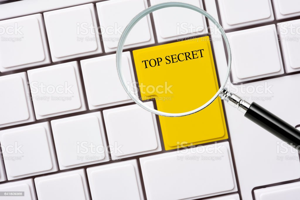 "High angle view of ""TOP SECRET"" yellow enter key of blank computer..."