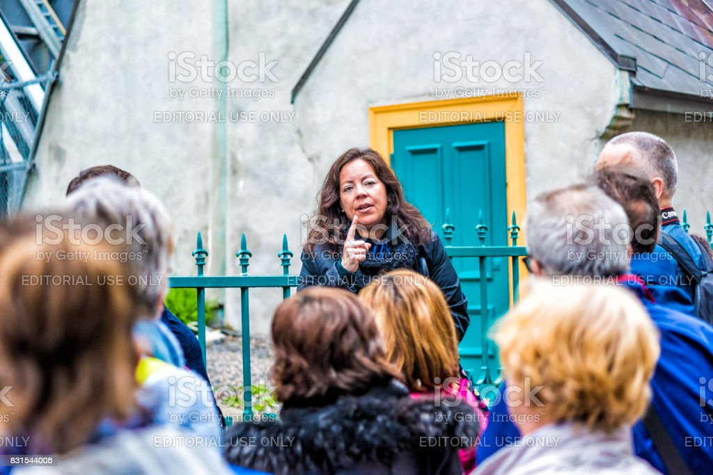 Closeup of tour guide emotionally gesturing and talking or explaining about old town history with group listening stock photo
