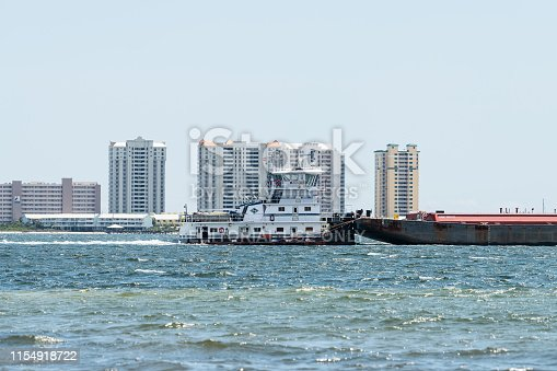 Navarre, USA - April 24, 2018: Closeup of towboat towing tank barge boat ship vessel in Pensacola bay at sea ocean shore of Gulf of Mexico, Florida Panhandle in Emerald coast