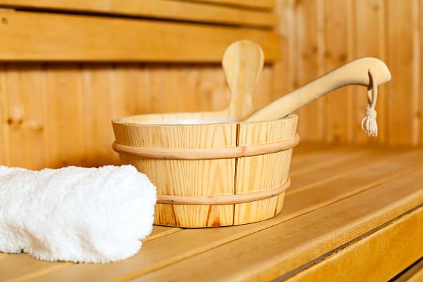nahaufnahme von handtuch, eimer und kelle in der sauna. - saunazubehör stock-fotos und bilder