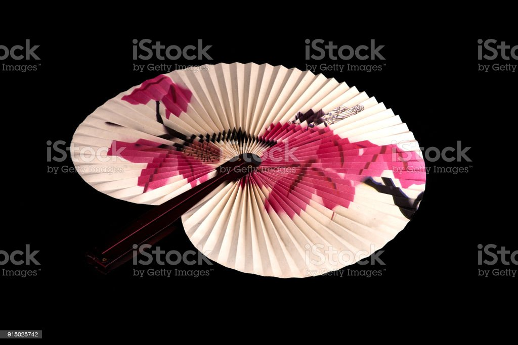 Closeup of Traditional Chinese paper fan on black background.Hand...