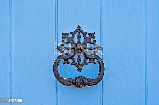 Closeup of traditional maltese door beater on blue wooden door. Vintage Forged carved knocker