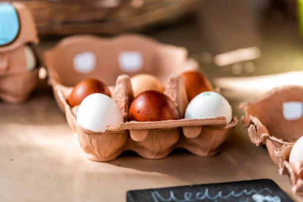 nahaufnahme des tabletts der farm frische braune und weiß bunte eier auf dem bauernmarkt in london, großbritannien - eierverpackung stock-fotos und bilder