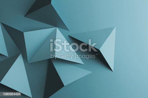 Composition with light blue papers folded in geometric shapes, texture background