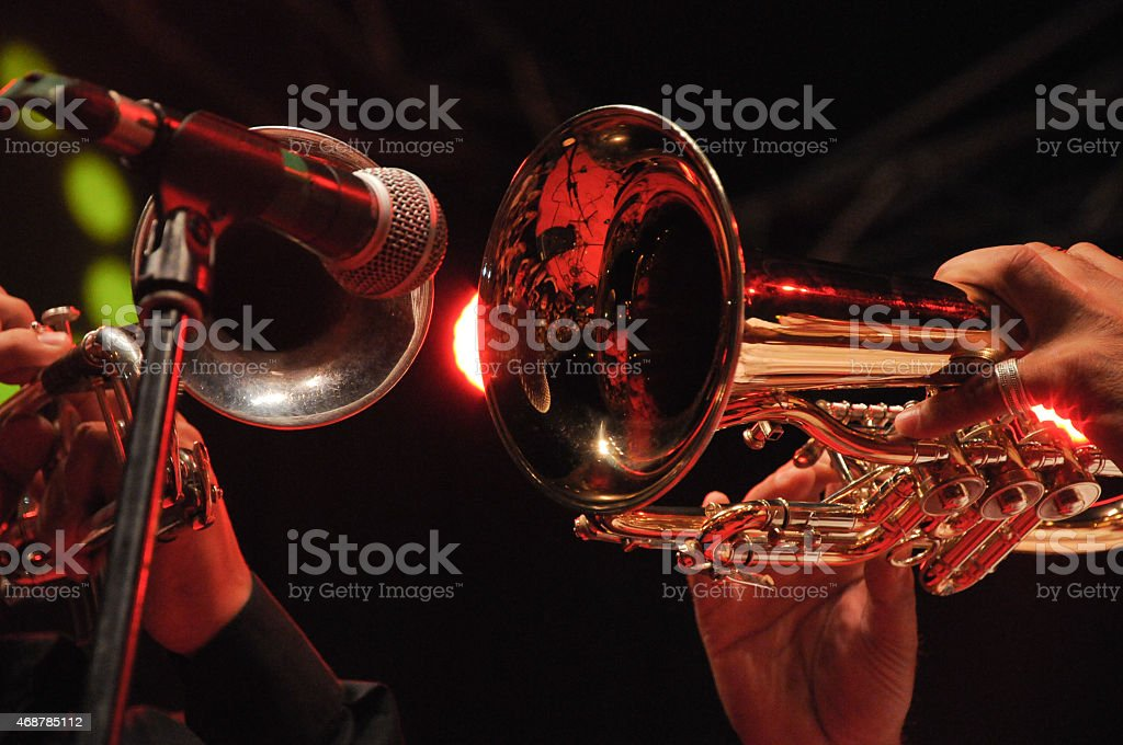 Close-up of trumpets being played into microphone Two men playing trumpets 2015 Stock Photo