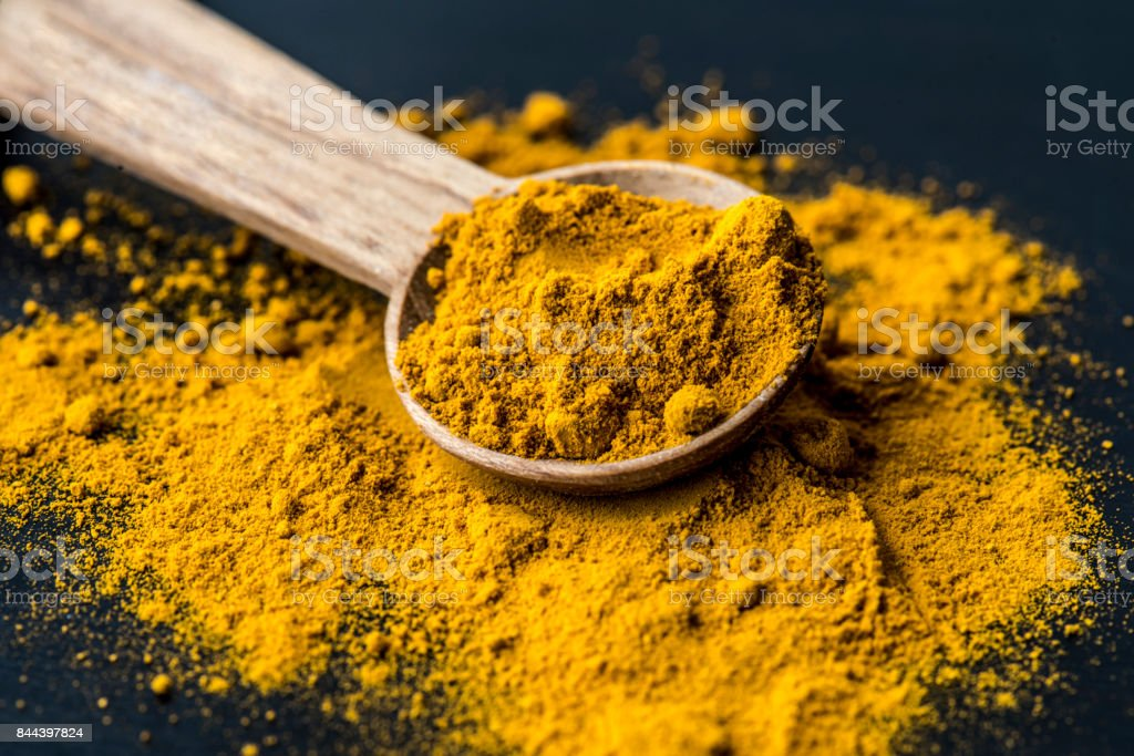 Closeup of tumeric powder spice on a spoon stock photo