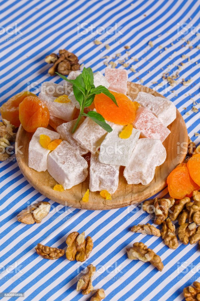 Close-up of turkish delight, dried apricots, bright leaves of mint and walnuts on a striped background, top view. stock photo