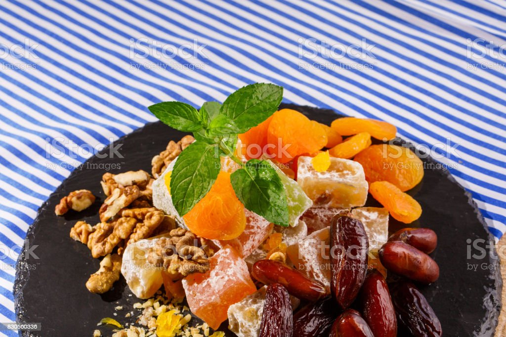 Closeup of turkish delight, walnuts and vivid fresh leaves of mint, date fruits on a glass plate on a glass background. stock photo
