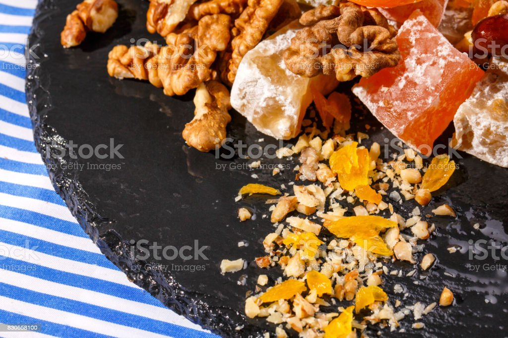 Closeup of turkish delights, date fruits, walnuts and bright green leaves of mint on a striped background. stock photo