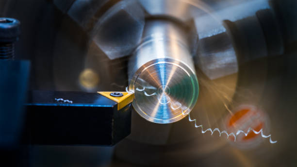 Close-up of turning with sharp tool bit on a dark background. Chip machining stock photo