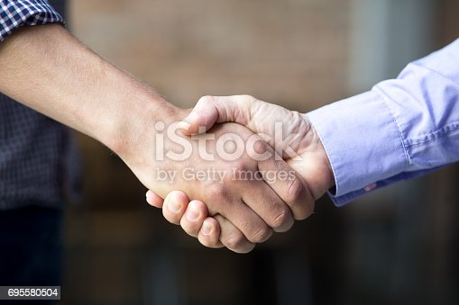 istock Closeup of Two Business Men Shaking Hands 695580504