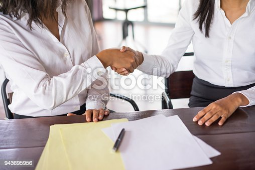 Closeup of two business women shaking hands and sitting at desk. There are blank papers on desk. Business agreement concept. Front view.