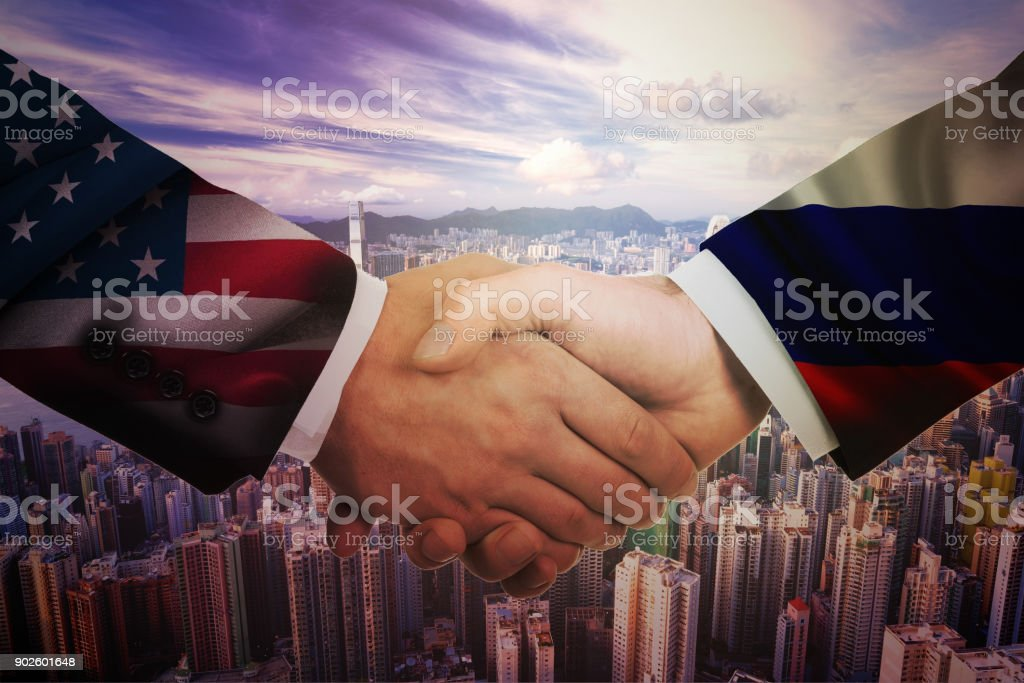 Close-up Of Two Businesspeople Shaking Hands In Front Of Us And Russia Flags On Table stock photo