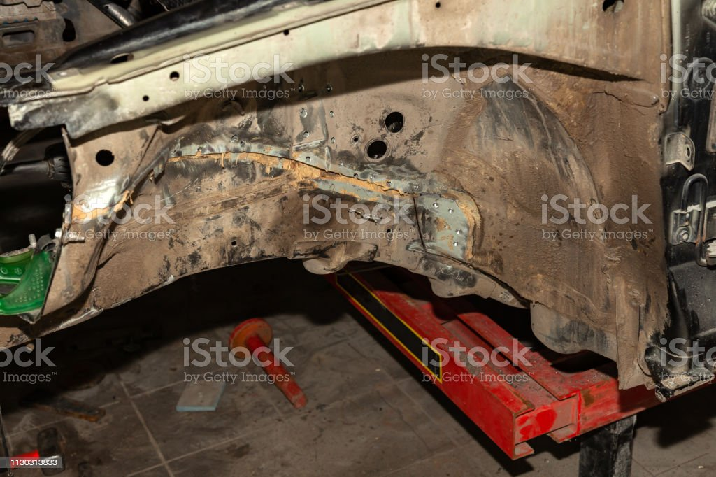 Close-up of two car body parts connected by spot welding after an...