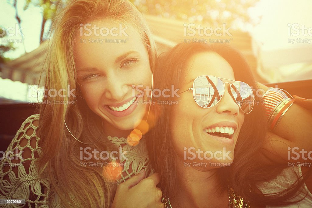 Close-up of two cheerful friends having fun at a cafe royalty-free stock photo