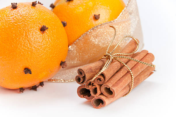 Closeup of two cloves-decorated oranges and cinnamon sticks