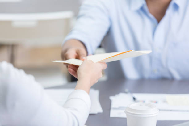 Closeup of two coworkers passing folder across table stock photo