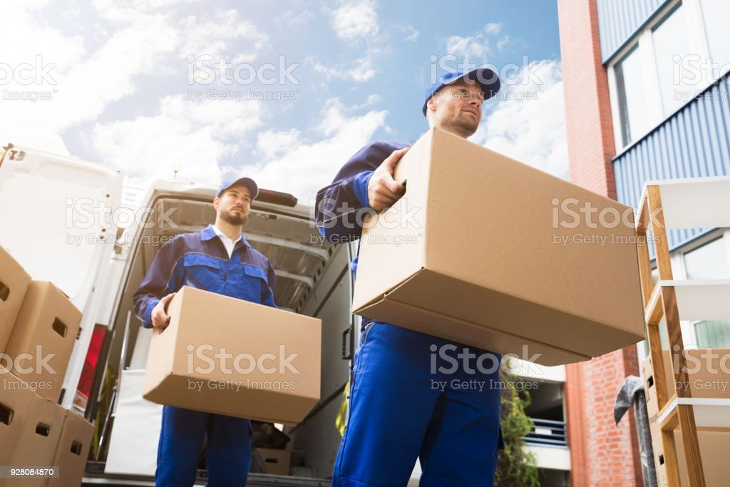 Close-up Of Two Delivery Men Carrying Cardboard Box stock photo