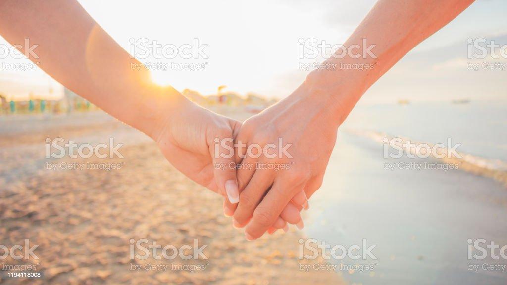 yakin cekim gun batimina karsi el ele tutusan iki kadin iki kiz el ile sahilde yuruyus escinsel lezbiyen cift ve kadin dostluk ve ask sevgililer gunu kavramikutlama stok fotograflar arkadaslik nin daha