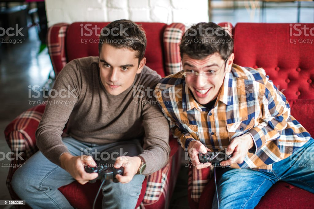 Closeup of two friends playing video game stock photo