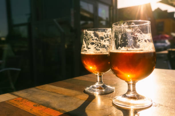Closeup of two glasses of beer on terrace table with evening sun shining through them. Relaxation, food and drink concept with copy space. stock photo