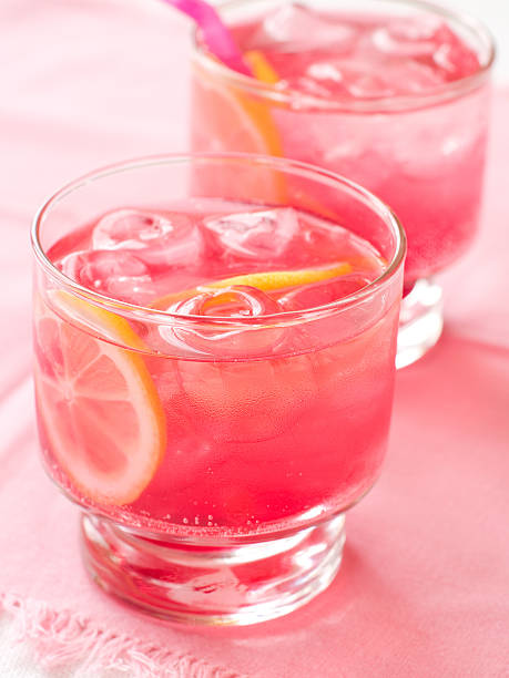 Close-up of two glasses with pink drinks and lemon garnish stock photo