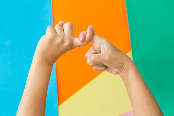close-up of two hands doing a pinky swear gesture - pinky promise stock photos and pictures