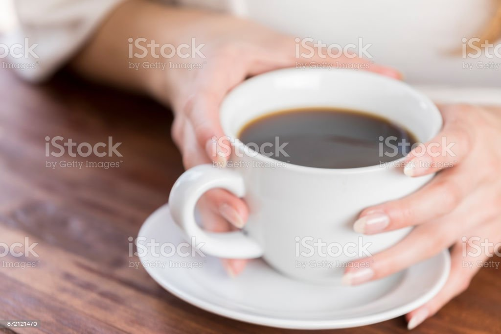 Closeup of two hands wrapped around coffee cup on table stock photo